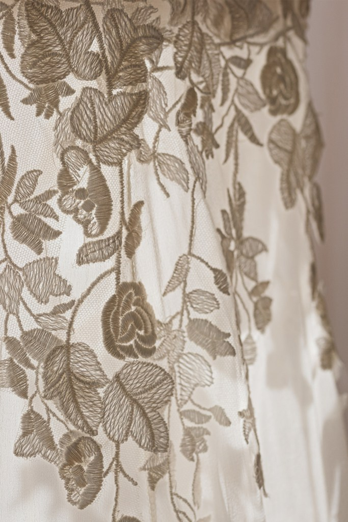 A close up of a bridal gown with intricate flowers