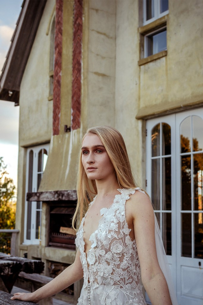A young woman in a white bridal gown stands on a balcony in front of a house
