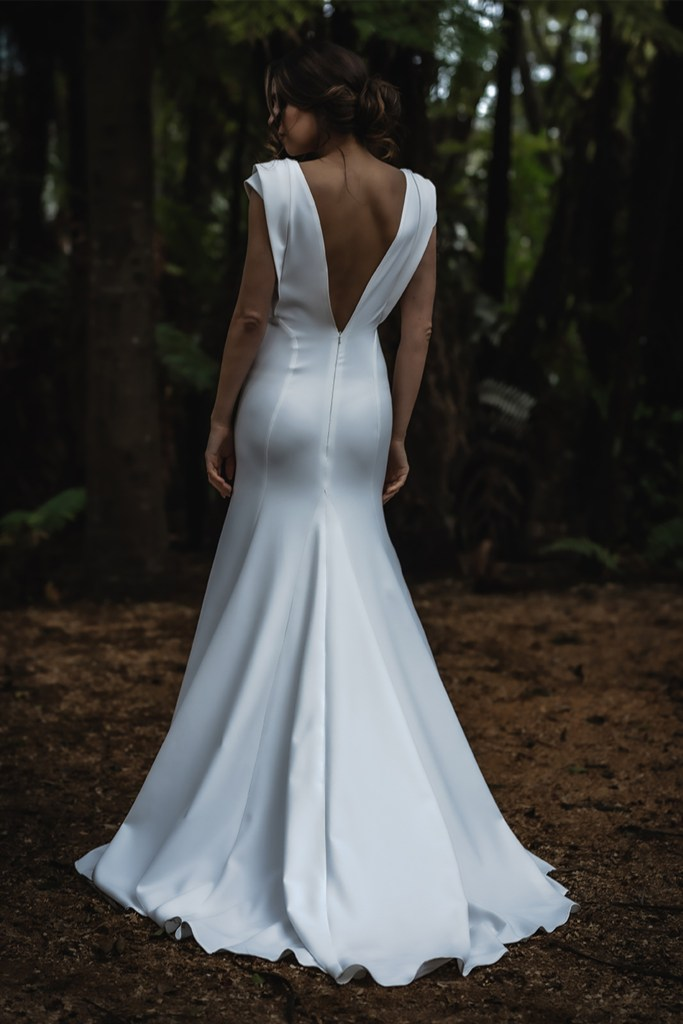 A woman wearing a white bridal gown stands in a wood with her back to the camera