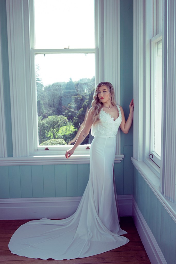 A woman stands in a room with big windows as she wears a wedding dress
