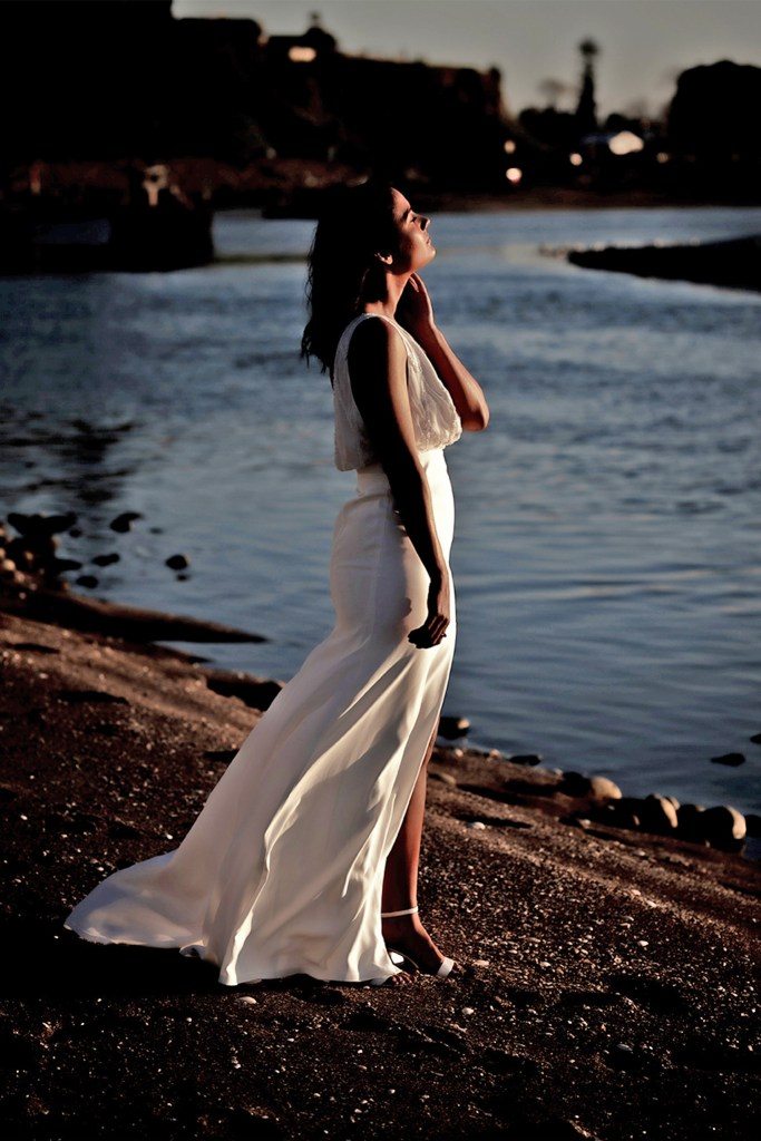 A woman in a white bridal gown stands on the edge of water