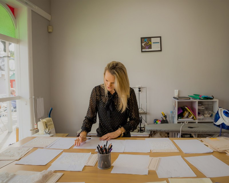 A woman standing at a desk with pieces of paper in front of her