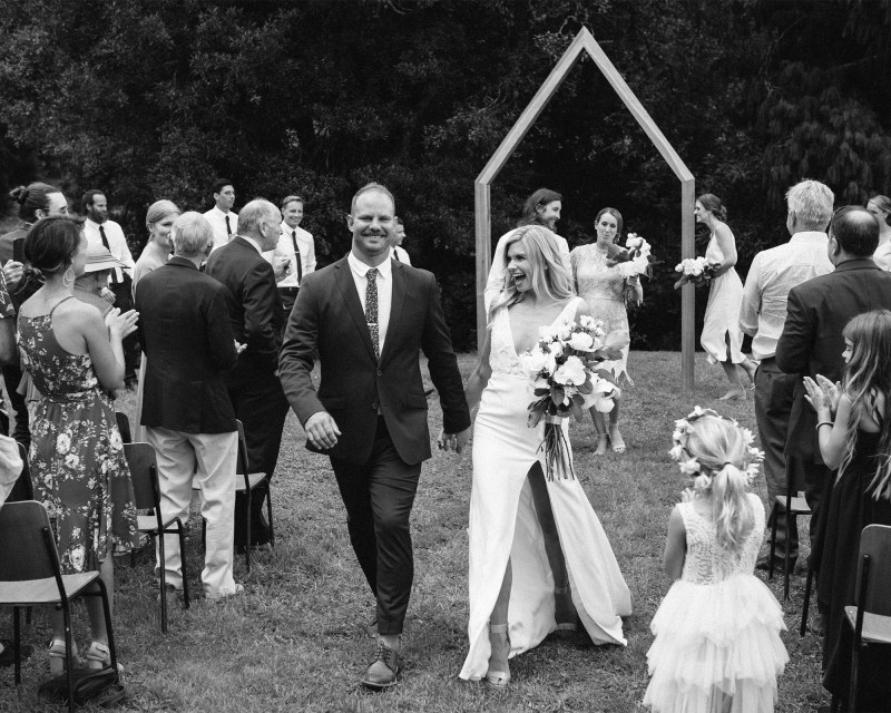 A groom and his bride walk down the aisle smiling after getting married