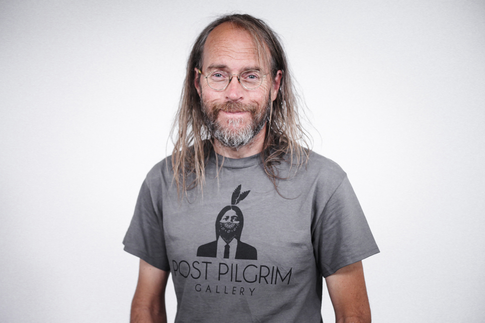Charlie Parr, from Duluth,MN, smiling for the camera in a Post Pilgrim Gallery shirt at the White Wall studio.