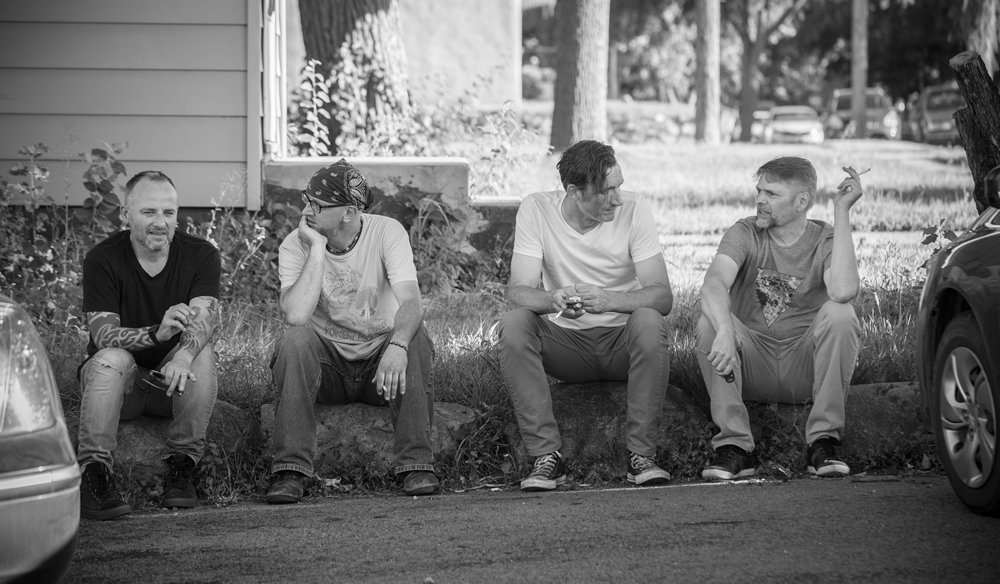 Sioux Falls rock band, Violet, sitting on the stoop at Last Stop CD Shop conversing and smoking.