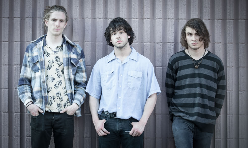 3 members of the Minneapolis Rock Band KICK, staring at the camera outside of Last Stop CD Shop in Sioux Falls.