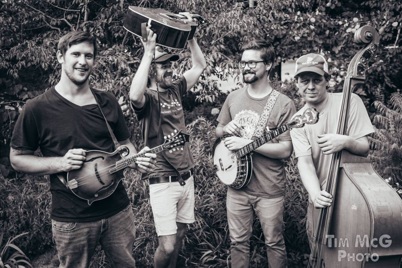 Black and white photo of Barbaro posing with their instruments outside