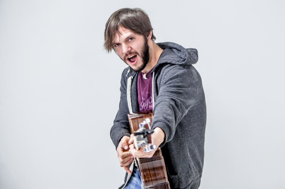 Maxwell Hughes poses with guitar as gun at the White Wall studio in Sioux Falls