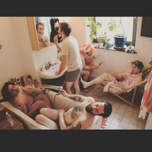 4 members of The Harmed Brothers sit in a bathroom in their underwear