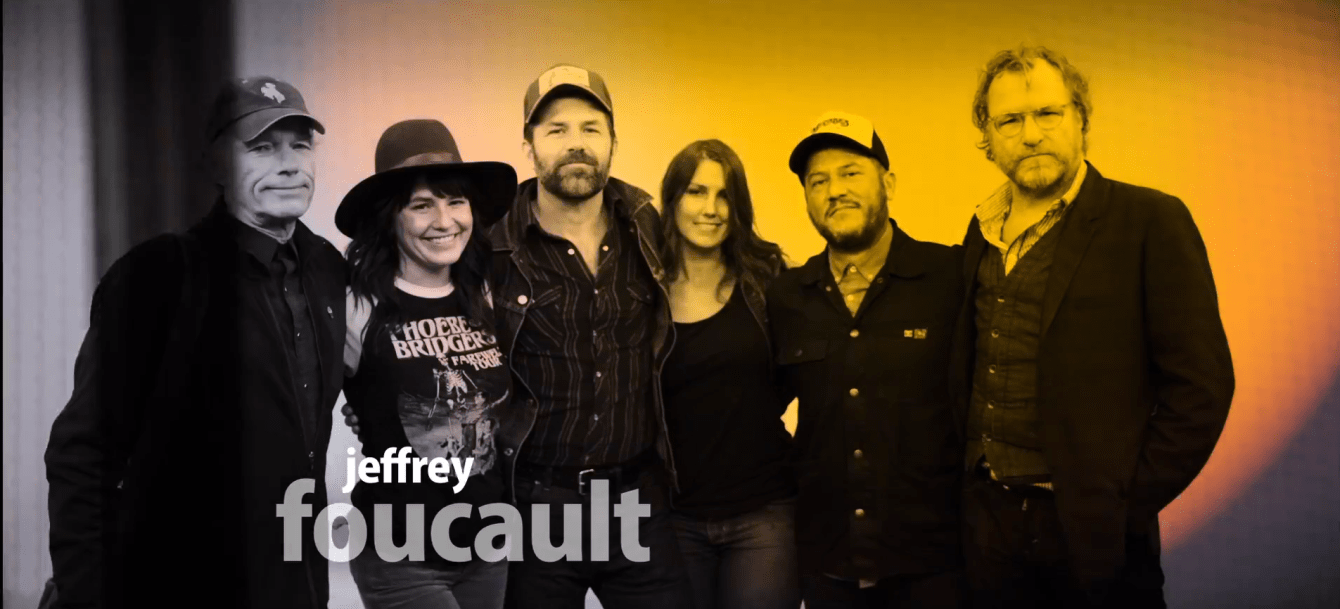 Jeffrey Foucault and band stand in a line smiling at the camera at Last Stop Studios