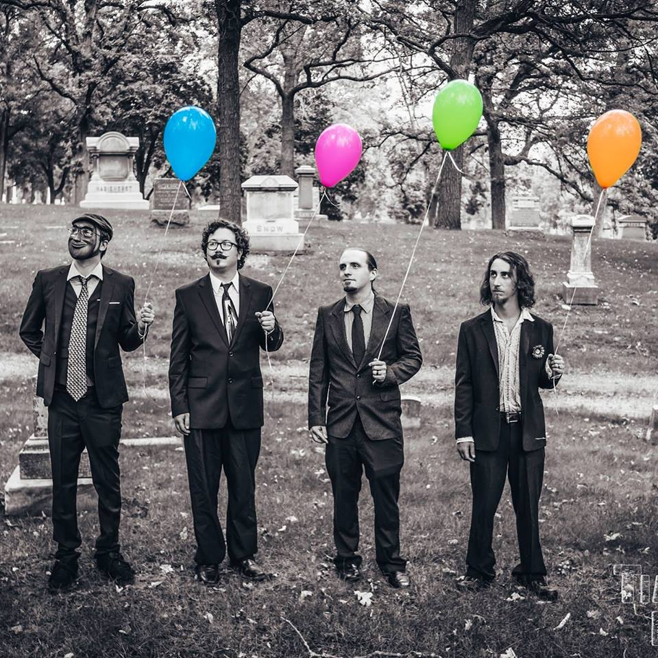 B&W image of 4 members of Dead Larry holding balloons in a line. The balloons hold all the color of the photo.