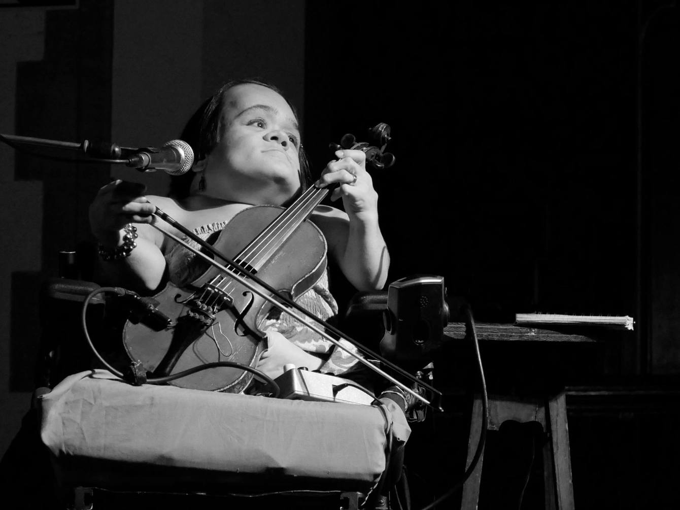 Gaelynn Lea holds her violin looking to the left in a black and white photo.