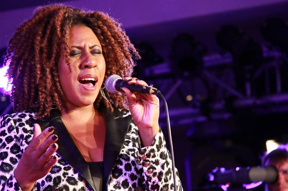 Minnesota soul singer, Annie Mack has her eyes shut singing into the microphone.