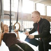 Male instructor helping a young female during a workout at gym on the rings. Personal trainer motivating young woman at health club.