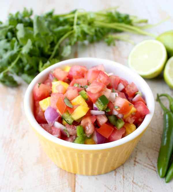 Toss this easy, homemade Tomato Mango Salsa recipe together in 5 minutes to serve on top of fresh fish, tacos or with chips for dipping!