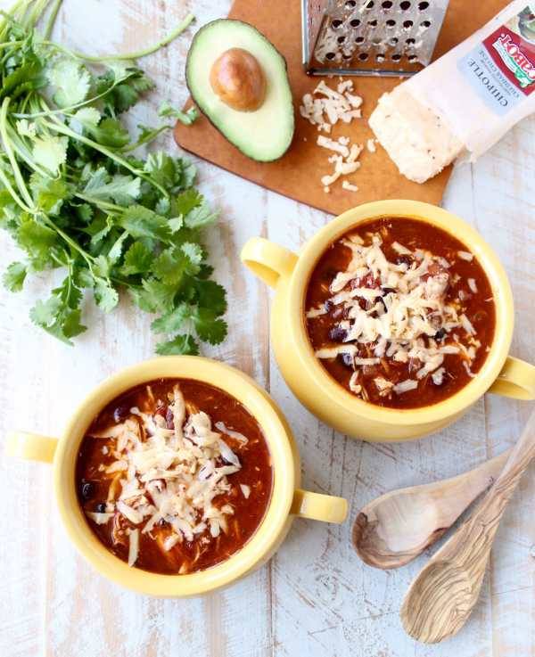 This Slow Cooker Chicken Enchilada Soup recipe is easy to prep in only 10 minutes & given a deliciously spicy kick with the addition of Sriracha!