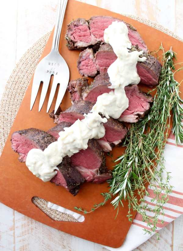An oven roasted herb crusted beef tenderloin is a show stopping dinner recipe, served with a mouth-watering creamy horseradish gorgonzola sauce.