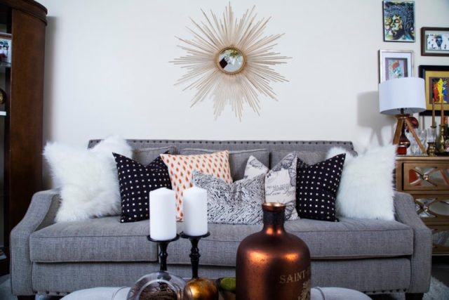 neutral living room | cream recliner | gold studs pillow | leather bookcase | neutral with pop of orange | gold sunburst mirror | eclectic bar cart | britt smith photography