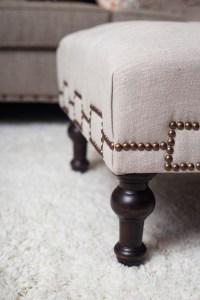 neutral living room   gray nailhead sofa   gold studs pillow   white fur pillow   neutral with pop of orange   cream nailhead ottoman   britt smith photography