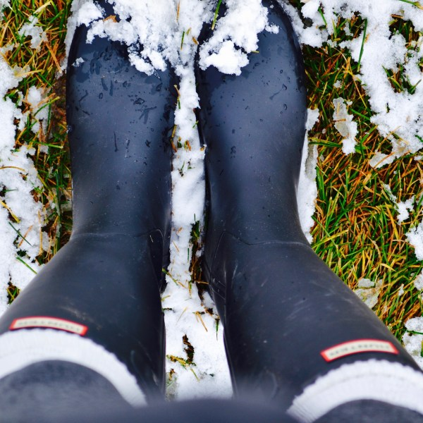 Black hunter boots in snow with tall white knee high socks to keep feet warm.