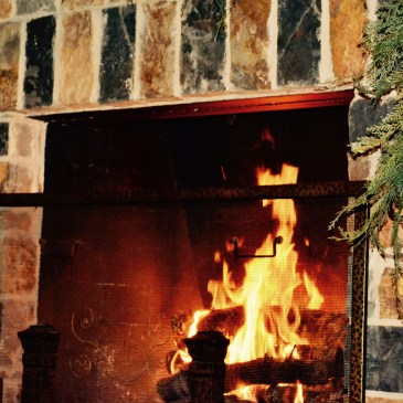 A red and yellow fire burning in a brick fireplace during the holidays.