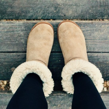 A tan pair of boots with white fur on the top over black leggings on wooden stairs.