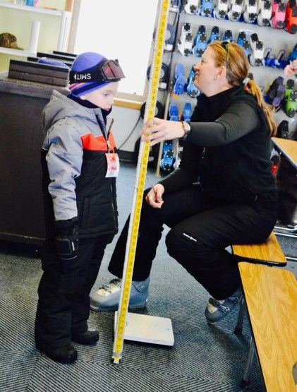 Measuring my son for his skis, boots, helmet.