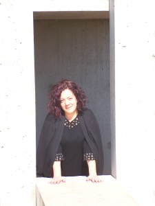 Portrait of a smiling woman wearing black, standing in a sunny doorway.
