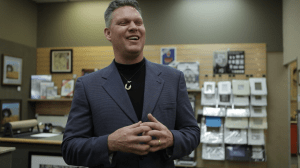Jeff Black wears a suit and smiles in front of a display of art and frames on the wall.