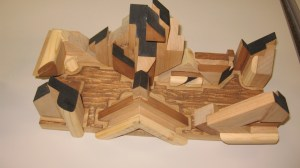 An intricate three-dimensional wood carving showing a representation of a city scape. The wood is blonde, and tops of buildings are black.