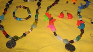 Two beaded necklaces, a bracelet, and a set of earrings all handmade. Some colors are earth tones, and some are bright and vibrant. Pendants are foreign coins.