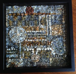 A shadow box with black frame on a dark wood table. Inside the box is an intricate, geometrical design with tiny, densely packed pieces of beach glass. Colors include blues, browns, whites, and yellows. Designs include circles, bars, lines, and stripes.
