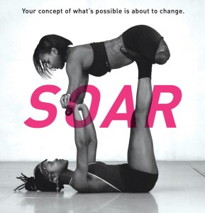 "A black and white image of two female, African-American dancers with ""SOAR"" in large pink lettering and the sentence ""Your concept of what's possible is about to change."" One dancer lies on her back with her arms and legs facing up, holding aloft the second dancer, whose arms and legs are shortened from being amputated early in life."