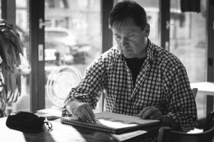 Black and white photo of Rodney Bentley sitting at a coffee shop table, sketching in an artist pad.