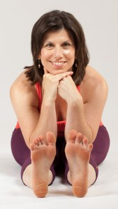 A white woman in yoga clothes sits on the floor and leans forward over straightened legs, rests her face on her hands, and smiles for the camera.