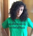 "Photo of Cheryl Green, looking annoyed, wearing a green shirt with ""My other disability is a bad attitude"" in black lettering."