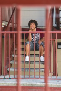 Dani sits on the steps of her apartment, smiling.