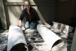Kris Haas kneels on the ground, unrolling 18-foot sheets of paper with black and gray ink paintings.