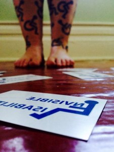 "Arianna's legs covered in temporary tattoos of the universal wheelchair access logo. On the ground lie temporary tattoos of the figure without the wheelchair and words ""invisible disabilities."" The figure's body takes the place of the first ""i"" in ""invisible."""