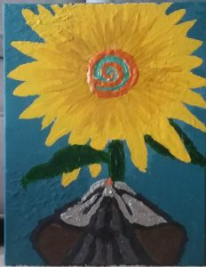 Thick, textured acrylic painting from above. A gray striped cat leans its head toward a frilly sunflower, its seeds a bright, orange spiral in the center.