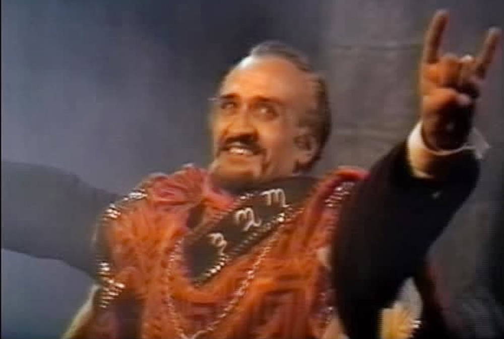 Delago as The Master delivers a rock'n'roll hail satan salute in Classic Who serial The Daemons