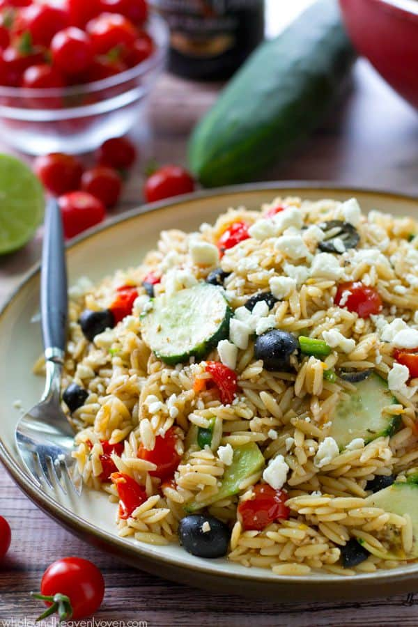 This colorful Greek-style orzo pasta salad is loaded with plenty of herbed sweet cherry tomatoes and is tossed in a light balsamic vinaigrette for one stunning summer salad! @WholeHeavenly