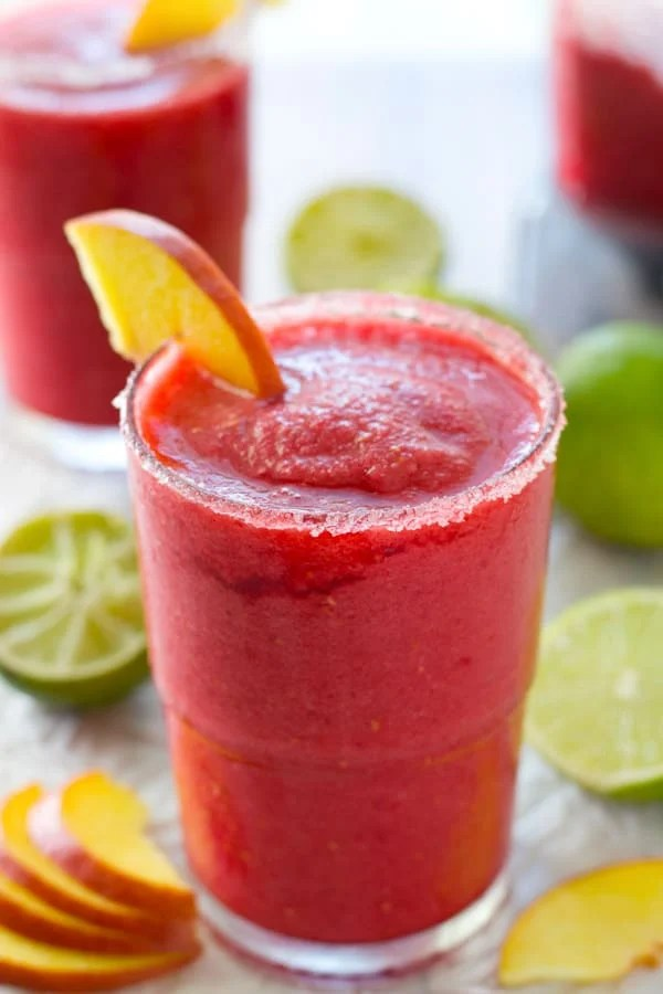 These spiked cocktail slushies are just exploding with summery peaches and raspberries! Whip 'em up in 5 minutes and sip the weekend away in style! @WholeHeavenly