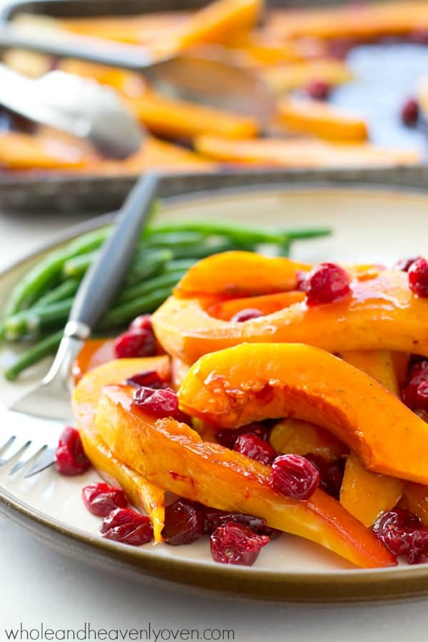 Butternut squash and cranberries are roasted to perfection in tons of honey and olive oil for one stunning side dish perfect for Thanksgiving or any fall dinner!