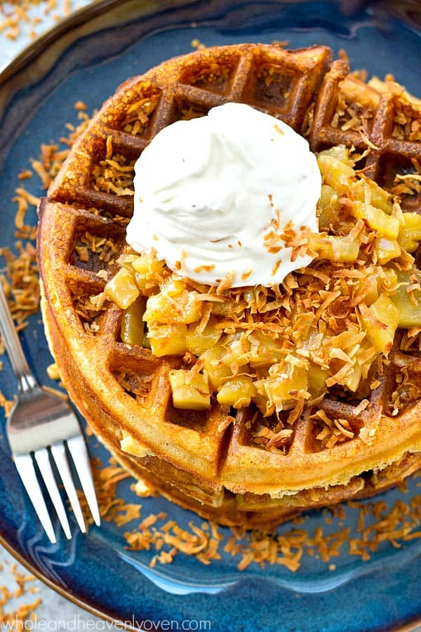 Light and unbelievably crispy yeast waffles where the batter is made overnight, cooked in the morning, then topped with a warm pineapple pina colada topping and plenty of whipped cream!