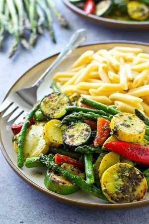 Covered in flavorful pesto and grilled to smoky perfection, these grilled vegetables and penne pasta are an easy and totally amazing vegetarian dinner for the summer!