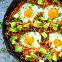 This loaded breakfast skillet features gorgeous baked eggs on a bed of crispy sweet potato hash browns with tons of avocado and Parmesan cheese on top.---ideal for a healthier weekend brunch!