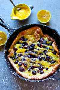 This blueberry lemon curd dutch baby combines the BEST flavors of juicy blueberries and tangy homemade lemon curd all piled into a big, flaky dutch baby! Easiest fancy breakfast ever.