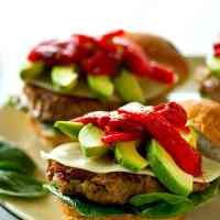 Unbelievably juicy and packed with summer flavors, these roasted red pepper avocado chicken burgers are a lighter and SUPER flavorful burger to throw on the grill all summer!