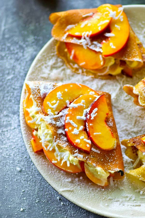 Melt-in-your-mouth coconut crepes are filled with a soft whipped cream filling and piled high with tons of juicy peaches for the ultimate stunner summer breakfast!